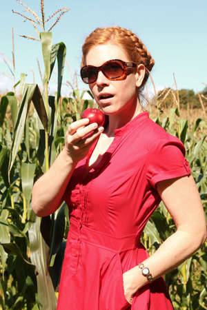 Woman with a red dress eating a red apple by a nice day photo