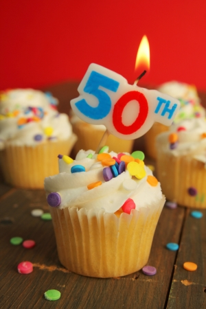 Delicious cupcake with 50th candle on top and 49 other cakes in background photo