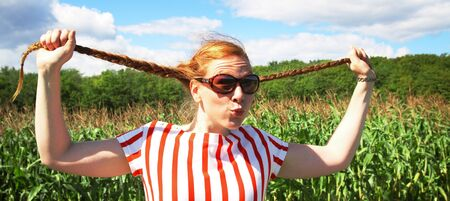 happier: Red hair girl holding braids in hands  Stock Photo
