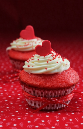 Red velvet cupcakes with a red heart on top on a red background photo