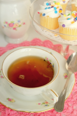 Delicious tea in a nice cup with little cakes