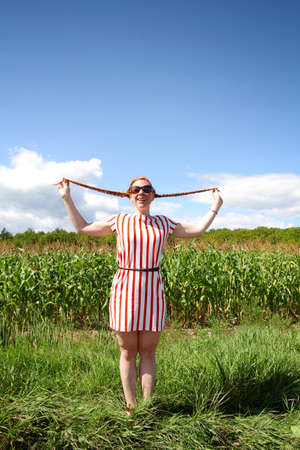 happier: Red hair girl holding braids in hands in a field