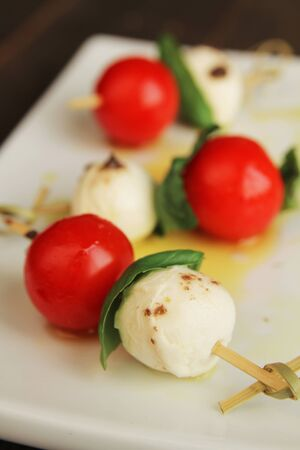 Top view of delicious skewer with boccocini, cherry tomatoes and basil or caprese