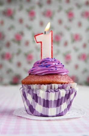 Purple cupcake with a number one candle on it photo