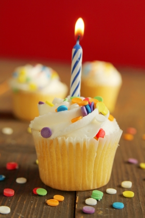 birthday cupcake: Cupcakes with colorful sprinkles and a blue candle on top Stock Photo
