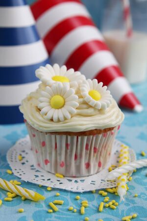first day: Cupcake with daisy on top and birthday hats in background