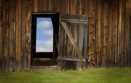 Blue sky behind a barn door in wood Stock Photo