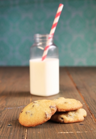 Chocolate chips cookies on wooden table and a bottle of milk in the background