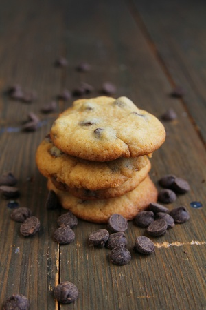 Pile of chocolate chips cookies surrounded by chocolate chips  Reklamní fotografie