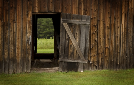 Open door on a rural landscape with a wooden barn wall