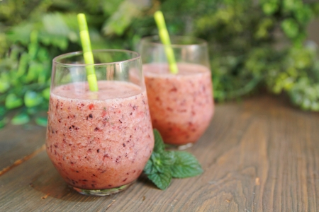 strawberry smoothie: Berry smoothie with green straw on a pink background
