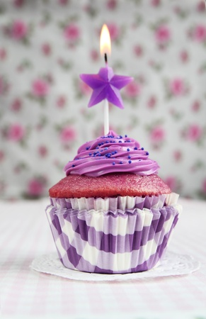 Purple cupcake with a star candle on it photo