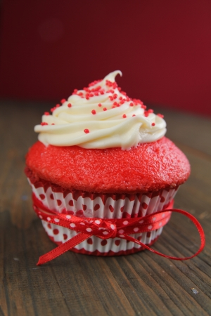 red velvet cupcake: Red velvet cupcake with a red ribbon on a wooden table