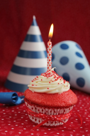red velvet cupcake: Red velvet cupcake with blue birthday hats on a red background