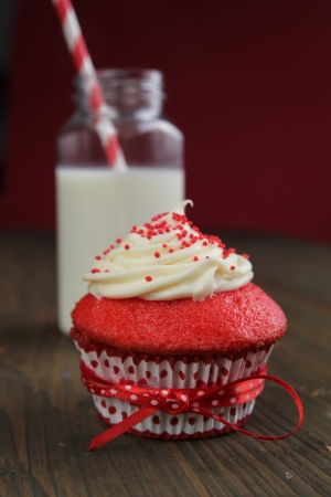 red velvet cupcake: Red velvet cupcake with a glass of milk with lined straw on a red background Stock Photo