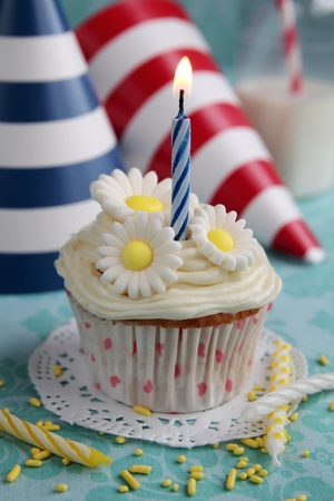 Cupcake with daisy on top and birthday hats in background photo