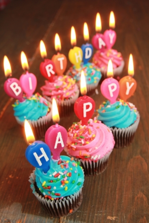 Pink and blue icing cupcakes with candles saying happy birthday Stock Photo