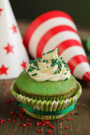 Green birthday cupcake with hats in background photo