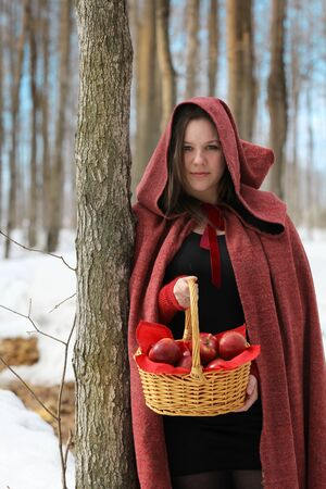 woman wearing a red hooded cloak and holding a basket full of red apples have a break in a forest photo