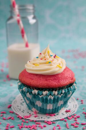 Pink cupcake with a glass of milk with lined straw on a aqua background Stock Photo - 21377063