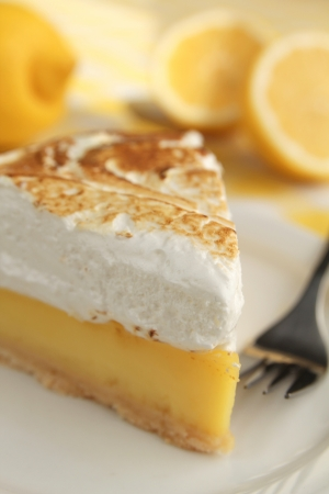 Lemon pie with meringue and a fork in a plate photo