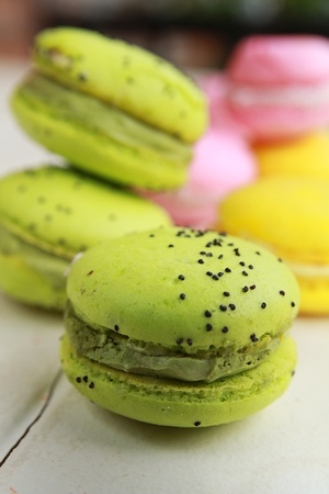 Pistachios macarons on a table with pink and yellow macarons Stock Photo