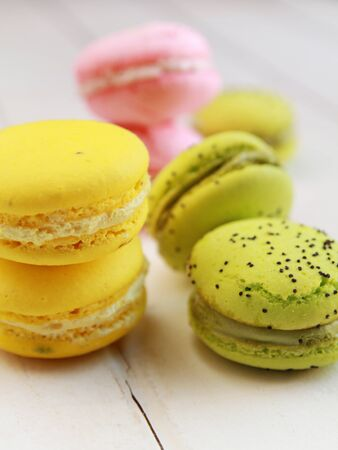 Green, yellow and pink macarons on a table