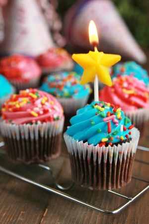 Birthday cupcakes with star candle on a table photo