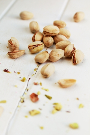 Bunch of pistachios and crunched pistachios in foreground