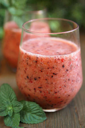 Berry smoothie with mint leave on a wooden table
