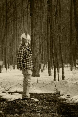 Man wearing a rooster mask in a forest looking at the camera in sepia photo