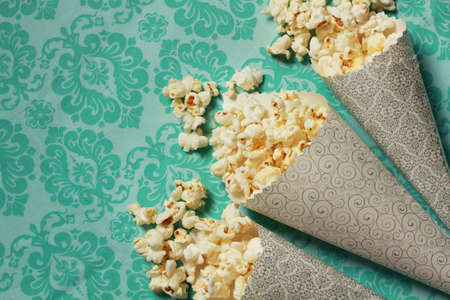 Three containers full on popcorn on a turquoise background 스톡 콘텐츠