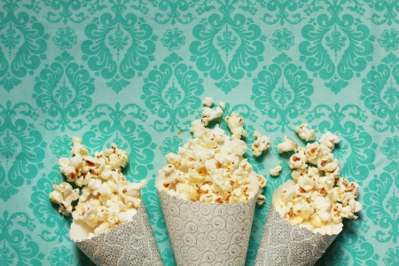 popcorn kernel: Three containers full on popcorn on a turquoise background Stock Photo