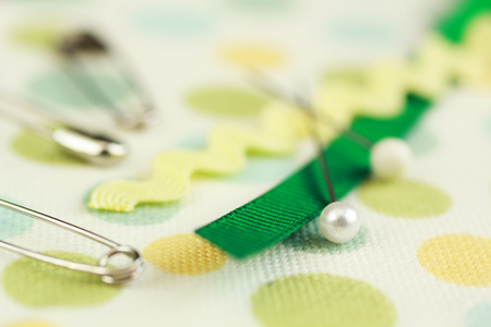 Safety pins and ribbons on a polka dots material photo