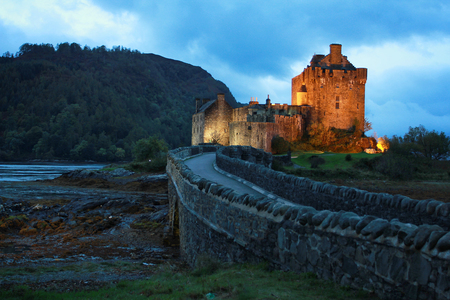 Eilean Donan castle illuminated at dusk, located in the Highlands, Scotland, UK.