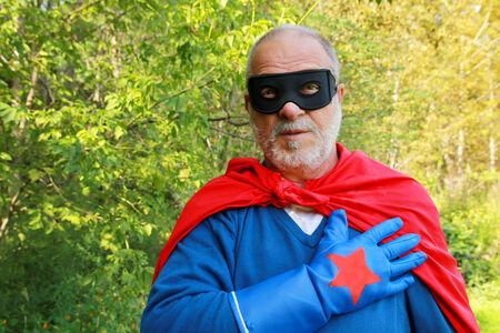 Senior man super held formeel met een hand op het hart Stockfoto