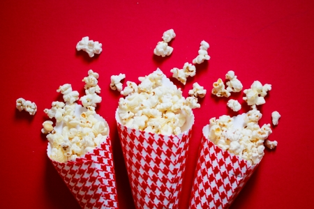 popcorn bowls: Three containers full on popcorn on a red background Stock Photo