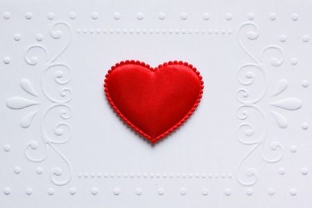 Blank embossed white paper with red satin hearts on it.   photo