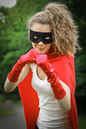 supergirl: Blond masked girl ready to fight wearing a red cape and red gloves Stock Photo