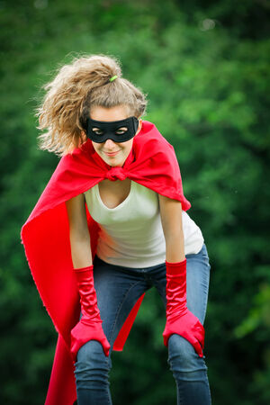 supergirl: Serious blond and caucasian woman with a mask and red hero suit