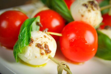 Close up of a bocconcini with basil and cherry tomatoes on skewer for appetiser