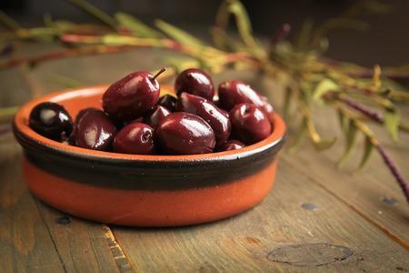 Kalamata olives into a bowl on wooden table photo