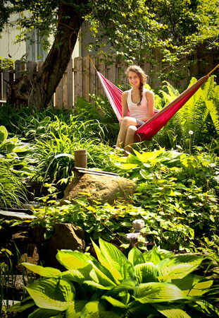 Young blonde teenager sit in a red hammock surround by green plants 写真素材