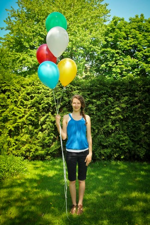 Teen standing on grass holding a bunch of balloons photo