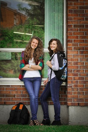Two students standing outside near the school with their bags and material school photo