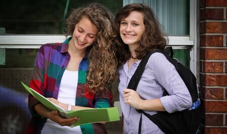 Two smiling students with their bags at school studying photo