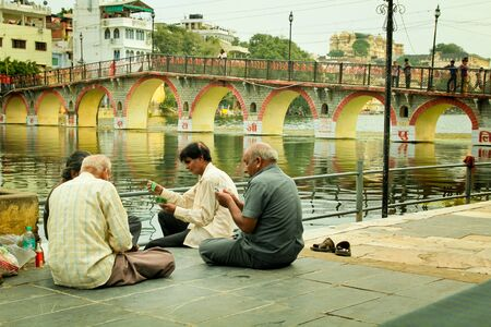 UDAIPUR - SEPT 20 2012:  Four man playing cards on the side of the Pichola lake at Udaipur also called Venice of the east.  Pichola lake is considered as one of the most beautiful in the state.  Editorial