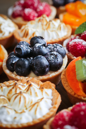 Lemon, raspberry, blueberry and peach tarts in a display