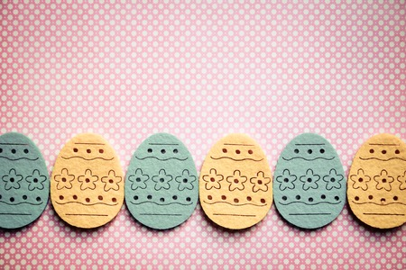 Decorated felt easter eggs yellow and blue on a pinky polka dots background   Vintage style