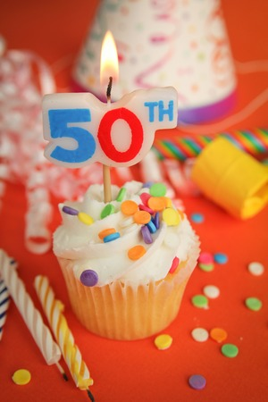 noisemaker: Delicious cupcake with 50th candle on top with hat, candle and noisemaker in background Stock Photo